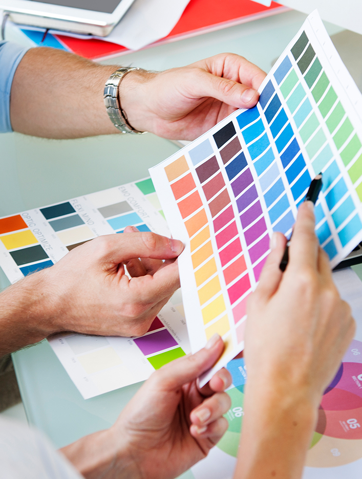 Kingstown Associates. Services. Design and Print. A woman and man looking at various pantone colour sheets.