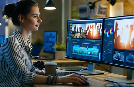 Kingstown Associates. Services. Design and Print. A woman editing images and a video on two separate iMacs.