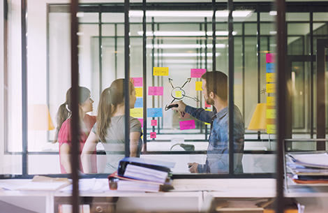 Kingstown Associates. Services. Design and Print. A man drawing on a whiteboard filled with sticky noting. He is pointing at some of the notes while talking to two women.