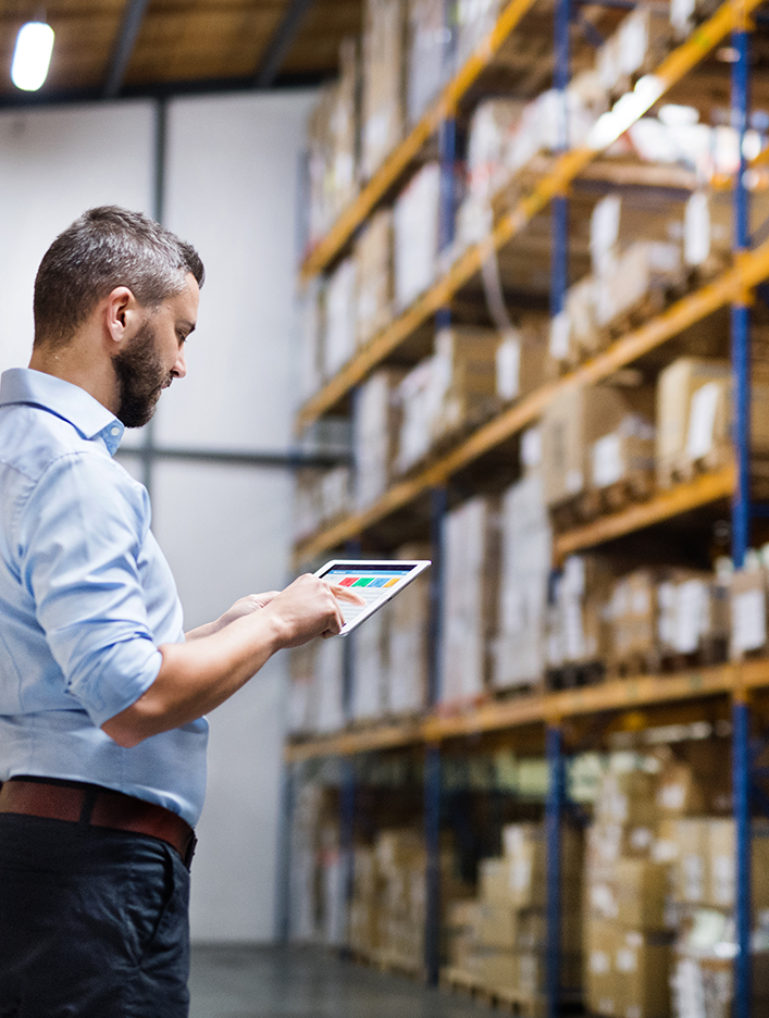 Kingstown Associates. Services. Fulfilment. A man looking at an ipad in a warehouse.